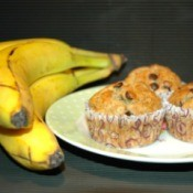 chocolate chip muffins on plate next to bunch of bananas