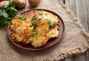 potato latkes on a brown plate with potatoes in background