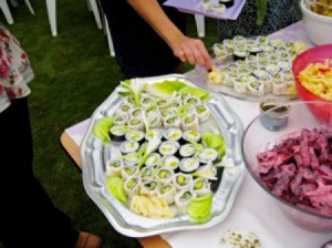 A potluck table at a wedding with rolled sushi and other foods.