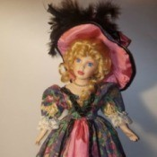 Identifying a Porcelain Doll - doll wearing a long floral dress with a dark pink under skirt and matching hat