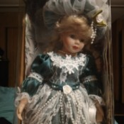 Identifying a Porcelain Doll - doll in box wearing a dark green dress with lace and pearls