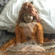 Identifying a Porcelain Doll - doll wearing a gold and lace dress