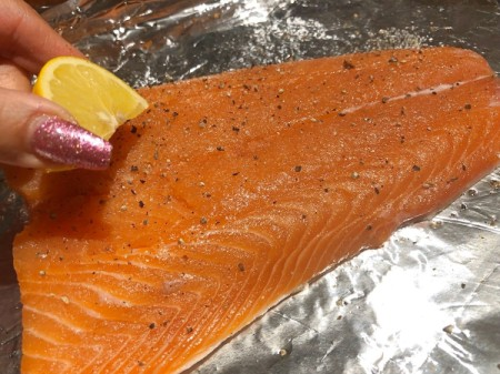 squeezing lemon on salmon