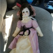 Identifying a Porcelain Doll - doll wearing a bonnet and an ecru dress with a pink over skirt