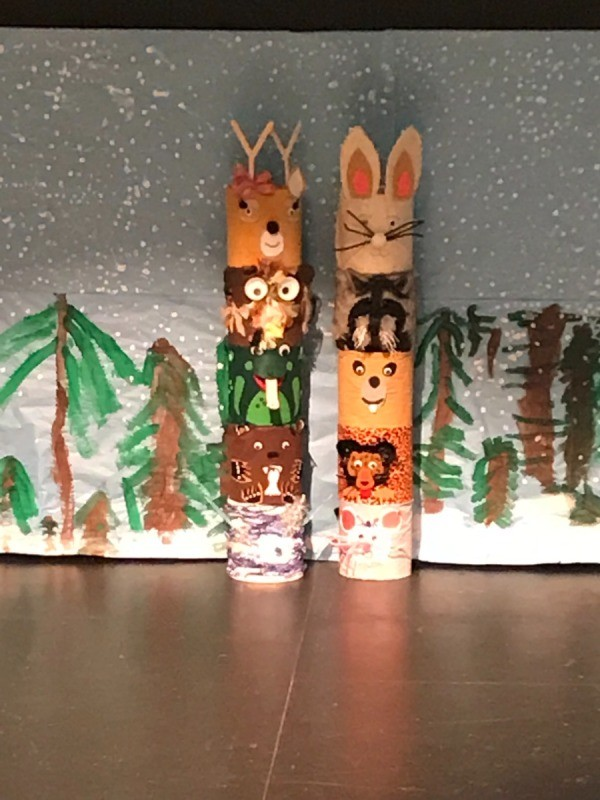 Ice Cream Bucket Frog Totem - two totem poles on a stage with a winter forest backdrop