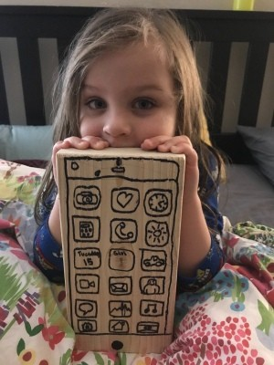 A play cellphone made from wood with drawn buttons.