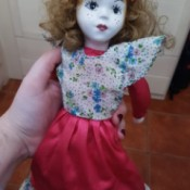 Age of a Porcelain Doll - doll wearing dress with floral bodice and red skirt