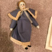 Identifying Porcelain Dolls - doll wearing long dress edged with lace, with matching cape