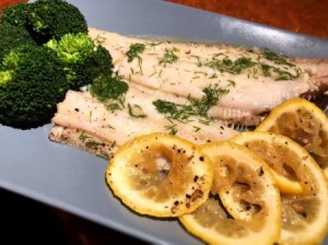cooked Fish, lemon and broccoli on platter