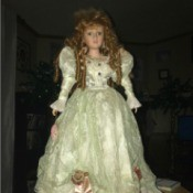 Identifying a Porcelain Doll  - doll wearing a long with dress with ribbon roses