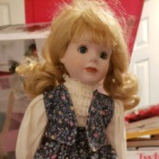 Identifying a Porcelain Doll - doll wearing a floral print skirt and vest