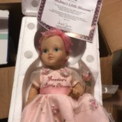 Value of an Ashton Drake Porcelain Doll - doll wearing a pink dress with embroidered flowers