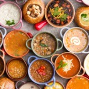 Many bowls of different varieties of soup.
