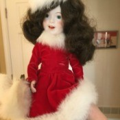Identifying a Porcelain Skater Doll - ice skater doll wearing a red dress and hat trimmed with white fur