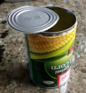 An empty can of corn with both the top and bottom removed.