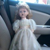 Identifying a Porcelain Doll - doll wearing a long white dress with a pink ribbon sash