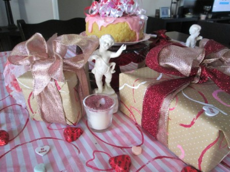 Recycled Paper Rolls as Heart Stamps - packages wrapped in the stamped paper sitting on a table covered with pink and white striped fabric stamped with red hearts