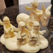 Information on a Tom Rubel Sculpture - ivory colored cast sculpture of 4 angels with one on a donkey