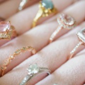 A collection of antique rings displayed on a pink display.