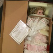 Determining the Value of a Porcelain Doll Collection - doll wearing a pink dress wrapped in plastic in a cardboard box