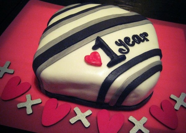 A decorated cake celebrating a 1 year anniversary.