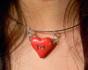 """A necklace with a big red heart and a """"M""""."""