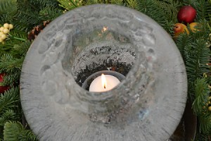 Round ice candle surrounded by greenery.