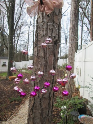 A wind chime made from a metal hanger and colorful bells.