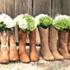 A row of boots with flowers for a country themed wedding.