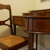 Value of a Vintage Desk and Chair - curved inlay wood desk with drawers and cubbies plus matching cane seat chair