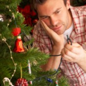 Man looking at a broken light on an Artificial Christmas Tree.