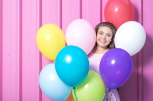 Young girl surrounded by colorful balloons.