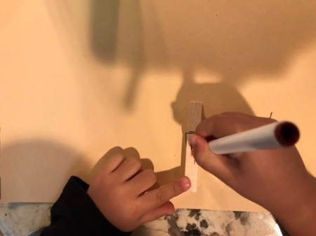 Imaginary Clothespin Flying Butterfly - child using a marker to decorate the clothespin