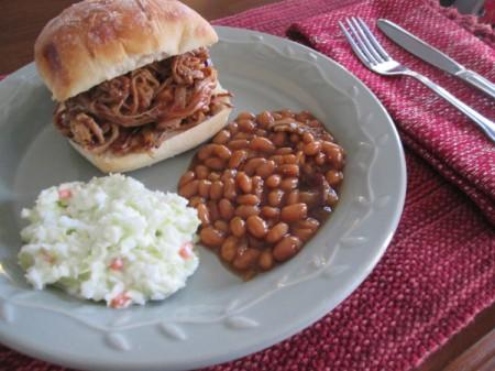 Pulled Pork sandwich, beans & coleslaw on plate
