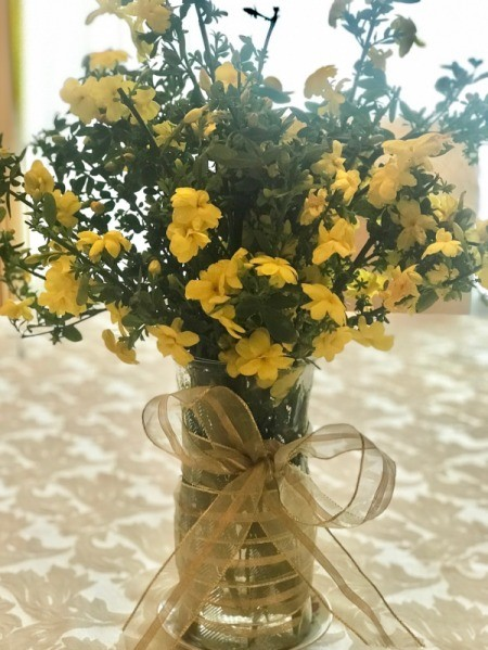 Yellow flowers in a vase decorated with ribbon.