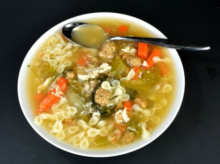 A bowl of Italian Wedding soup with meatballs, pasta, escarole and other veggies.