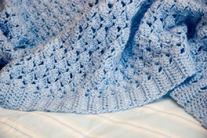 A blue blanket crocheted with a shell pattern.