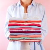 A woman holding a stack of folded laundry