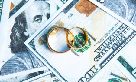 A pair of golden wedding bands on top of a spread out hundred dollar bills.