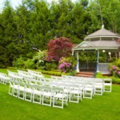Outdoor wedding with white folding chairs outside near a gazebo.
