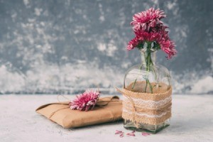 Small glass vase wrapped in burlap, lace and twine.