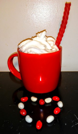 A licorice straw in a cup of hot chocolate.