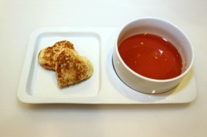 Grilled cheese hearts next to a bowl of tomato soup.