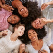 Group of teenagers laying in a circle laughing.