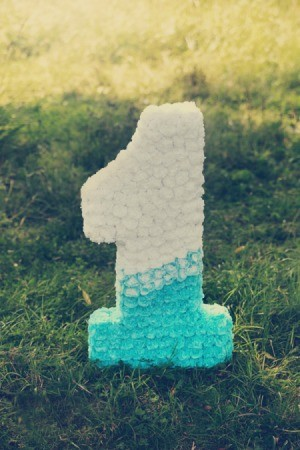 1 shaped Piñata sitting in the grass