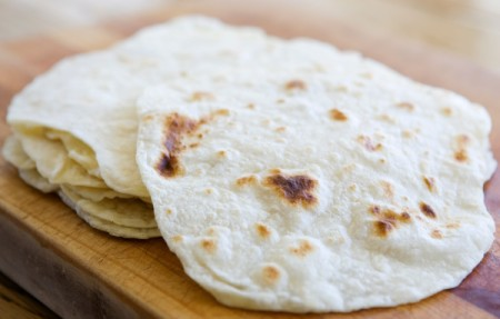 Homemade Tortillas piled on a cuttingboard