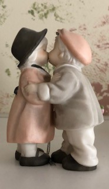 A figuring of two old fashioned children kissing.