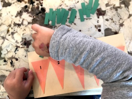 Carrot Counting Activity for Toddlers - child adding a leaf