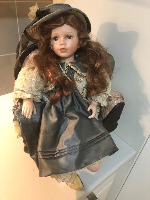Identifying a Porcelain Doll - doll wearing a gray dress and matching hat