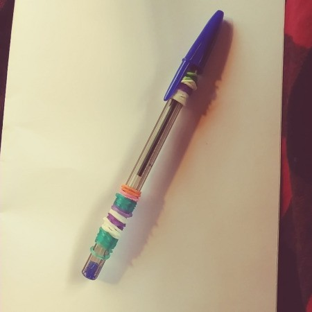 A pen with colorful rubber bands wrapped around it.